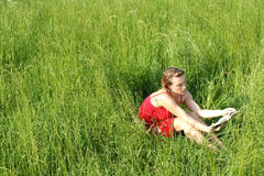 Reading in the grass II. Reading a book in a field of grass stock photography