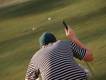Reading the Green. A young man reads the green while preparing to make a put on the golf course Royalty Free Stock Image