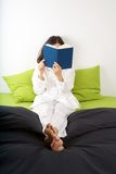Reading on green bed Royalty Free Stock Photography