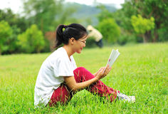 Reading on green grass Stock Image