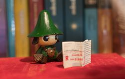 Reading green kid figure reading books in book shelf Royalty Free Stock Photos