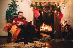 Reading guy on the background of Christmas tree and chimney stock photos