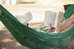 Reading in a hammock. Young woman reading a book while relaxing in a hammock Royalty Free Stock Photography