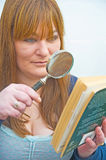Reading with a hand magnifier. Royalty Free Stock Images