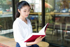 Reading her favorite book in cafe Stock Photography