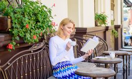 Reading is her hobby. Mug coffee and interesting book best combination perfect weekend. Woman have drink cafe terrace. Outdoors. Girl drink coffee while read stock photos