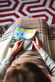 reading IKEA Catalogue on couch covered with blacnket Stock Photos