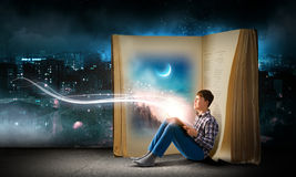 Reading and imagination. Teenager boy in jeans and shirt reading book Royalty Free Stock Photo