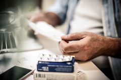 Reading instruction for using pill. Business senior man taking pill on work. Close up. Focus is on hand stock image
