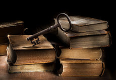 Reading is the Key. Conceptual still life image of old antique books and a big old key Stock Photos