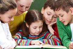 Reading kids. Portrait of friendly group reading book in classroom Stock Photography