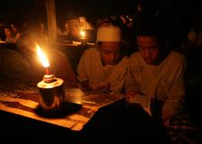 Reading koran using torch Royalty Free Stock Photography