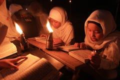Reading koran using torch Royalty Free Stock Image