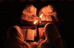 Reading koran using torch Stock Images