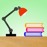 Reading-lamp and three books on a table Royalty Free Stock Photo