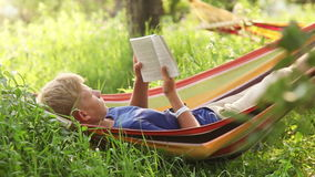 Reading last bestseller in cosy Hammock in apple trees shadows Royalty Free Stock Image