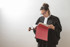 Reading the law. Thirty something brunette woman wearing a canadian lawyer toga with a gavel in her hands and reading a red criminal law book Stock Photos