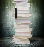 High stack of books with climbing businessman hang on it. Reading and learning a mountain of new knowledge concept. Climbing businessman hang on high stack of stock images