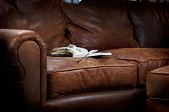 Reading on leather sofa Stock Image