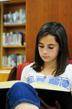 Reading in the Library. A tween schoolgirl studies in the library Stock Images