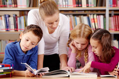 Reading in library. Portrait of pupils and teacher reading interesting book in library Stock Photos