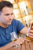 Reading a liquor label. Read Stock Photo
