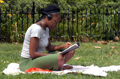 Reading and listening to music in the park. A young african american woman sits in the park and reads while listening to music royalty free stock image