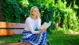Reading literature as hobby. Woman blonde take break relaxing in park reading book. Ultimate best book list. Girl keen. On book keep reading. Girl sit bench royalty free stock photo