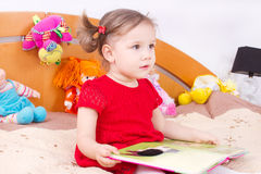 Reading little girl in bed Stock Image