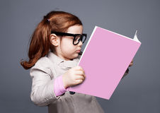 Reading love. Little girl with big glasses reading a pink book stock photo