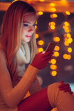 Reading lovely message from him. Beautiful young woman in white sweater holding smart phone and looking at it with smile and with defocused Christmas lights in Royalty Free Stock Photos