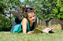 Reading a magazine. Young woman reading a magazine sitting on grass outdoors Royalty Free Stock Photography