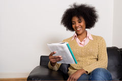 Reading magazine. Young woman reading a magazine at home Stock Images