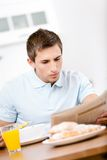 Reading male eats healthy breakfast in kitchen Stock Images