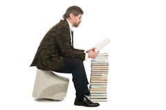 Reading man. Middle-aged man sitting on an old monitor and reads a book. Book instead of a computer Royalty Free Stock Photos