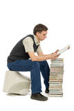 Reading man. Young man sitting on an old monitor and reads a book. Book instead of a computer Royalty Free Stock Photo