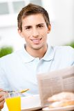 Reading man eats dieting breakfast in kitchen Stock Images