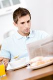 Reading man eats tasty breakfast in kitchen Royalty Free Stock Photography