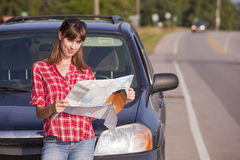 Reading a map. Young woman in front of a car on roadside reading a map Royalty Free Stock Photography