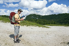 Reading a Map on the Trail. A hiker pauses to read a map while walking along a road in the Dolomites of northern Italy Stock Photo