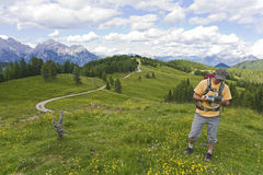 Reading a Map on the Trail. A hiker pauses to read a map while walking through meadows in the Dolomites of northern Italy Stock Photography