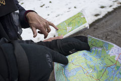 Reading maps. Two man are reading a map to find the right direction during a hike in a winter landscape Royalty Free Stock Photo