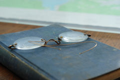 Reading Materials. This image is of an old hardback book and a pair of reading glasses Royalty Free Stock Photos