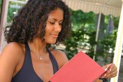 Reading the menu II. Beautiful brazilian woman reading the menu Stock Photography