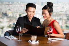 Reading menu. Vietnamese couple reading menu together in a restaurant Royalty Free Stock Image