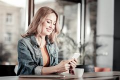 Happy smiling woman sitting in a cafe and reading messages Royalty Free Stock Images