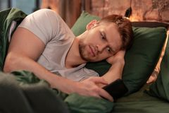 Bearded boyfriend feeling jealous reading messages of his woman. Reading messages. Dark-eyed bearded loving boyfriend feeling jealous reading messages of his royalty free stock image