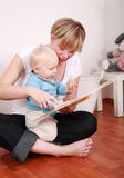 Reading with mom. Cute little boy looking at picture book with his mom Royalty Free Stock Photography