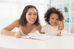 Reading with mom. Image of a smiling mom with her little daughter with a book posing at camera Royalty Free Stock Photos
