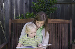 Reading with Mom. A mother reads a book to her young son as they sit quietly together on a wooden bench swing Royalty Free Stock Images